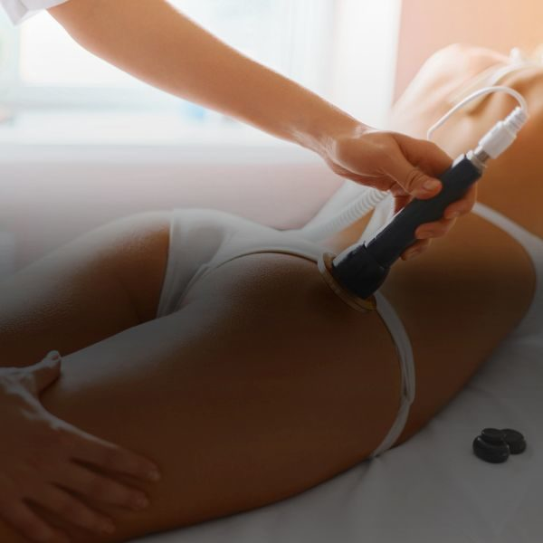 Body care. Spa treatment. Ultrasound cavitation body contouring treatment. Woman getting anti-cellulite and anti-fat therapy in beauty salon.